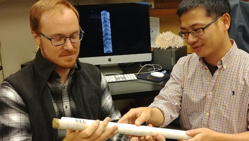 WHOI scientists Nathaniel Mollica (left) and Weifu Guo examine a core extracted from a coral skeleton. In a new study published in the Proceedings of the National Academy of Sciences, they showed how ocean acidification affects coral skeletal growth - photo © Anne Cohen Lab, WHOI