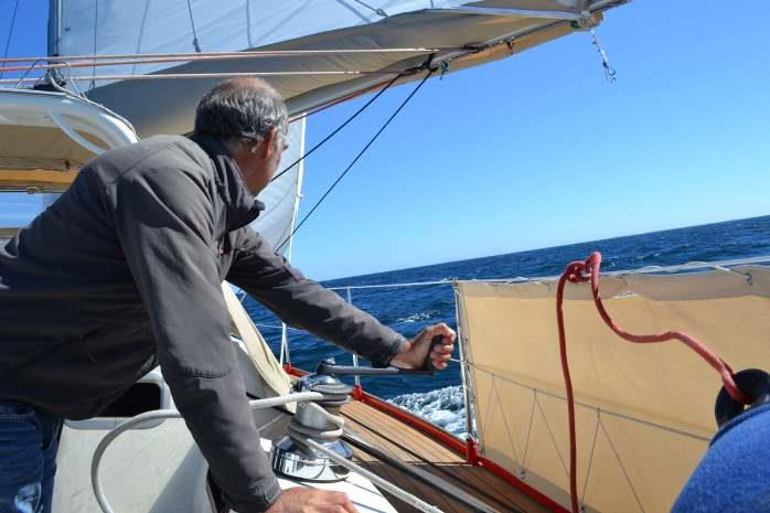 Captain sheeting the head sail on passage - photo © Maree & Phil