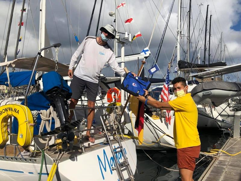 Montana receiving a skippers bag for ARC 2020 from ARC yellowshirt Alex photo copyright World Cruising taken at  and featuring the Cruising Yacht class
