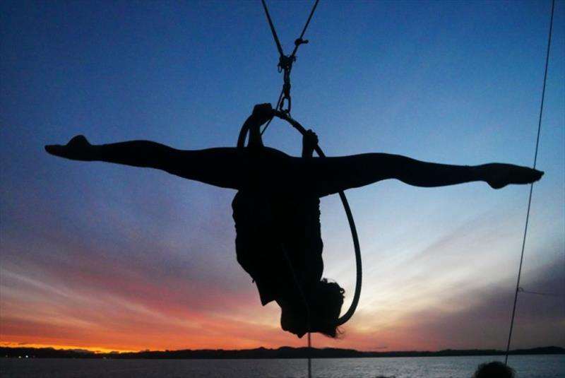 Not your average boat in the sunset silhouette: aerialist Rumah hard at work in the rigging. - photo © Jorge Rodriguez Roda